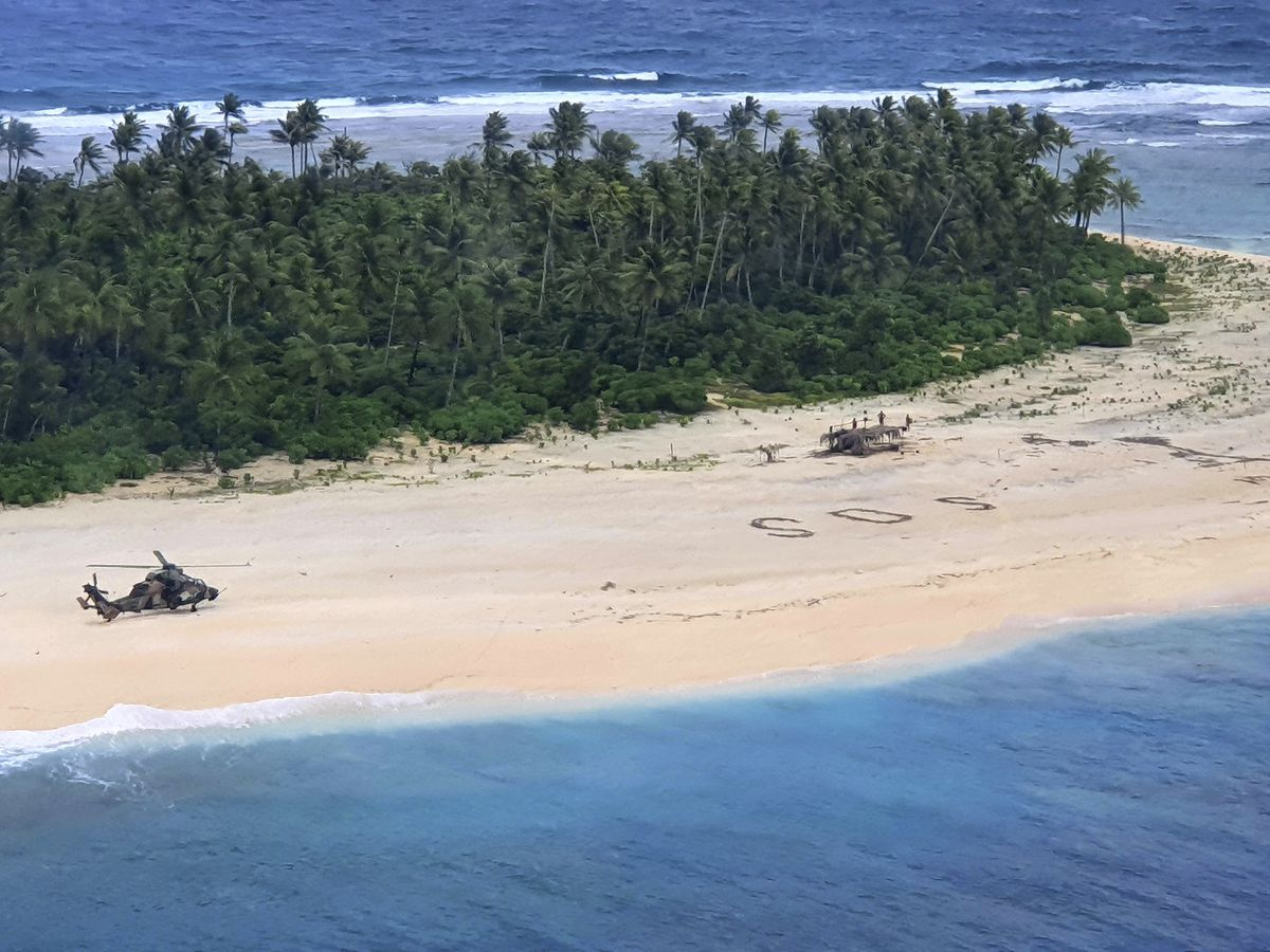In this photo provided by the Australian Defence Force, an Australian Army helicopter lands on Pikelot Island in the Federated States of Micronesia, where three men were found, Sunday, Aug. 2, 2020, safe and healthy after missing for three days. The men were missing in the Micronesia archipelago east of the Philippines for nearly three days when their