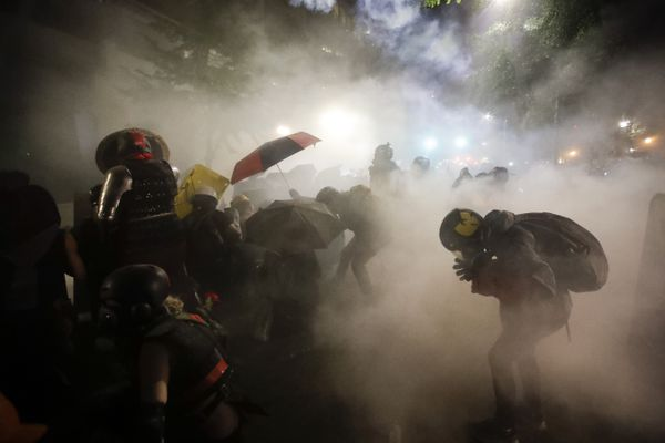 """FILE - In this July 26, 2020, file photo, federal officers launch tear gas at a group of demonstrators during a Black Lives Matter protest at the Mark O. Hatfield United States Courthouse in Portland, Ore. An Associated Press analysis of more than 200 arrests shows that even those accused of breaking the law during the nightly rallies don't neatly fit into President Donald Trump's depiction of protesters as """"anarchists and agitators."""" (AP Photo/Marcio Jose Sanchez, File)"""