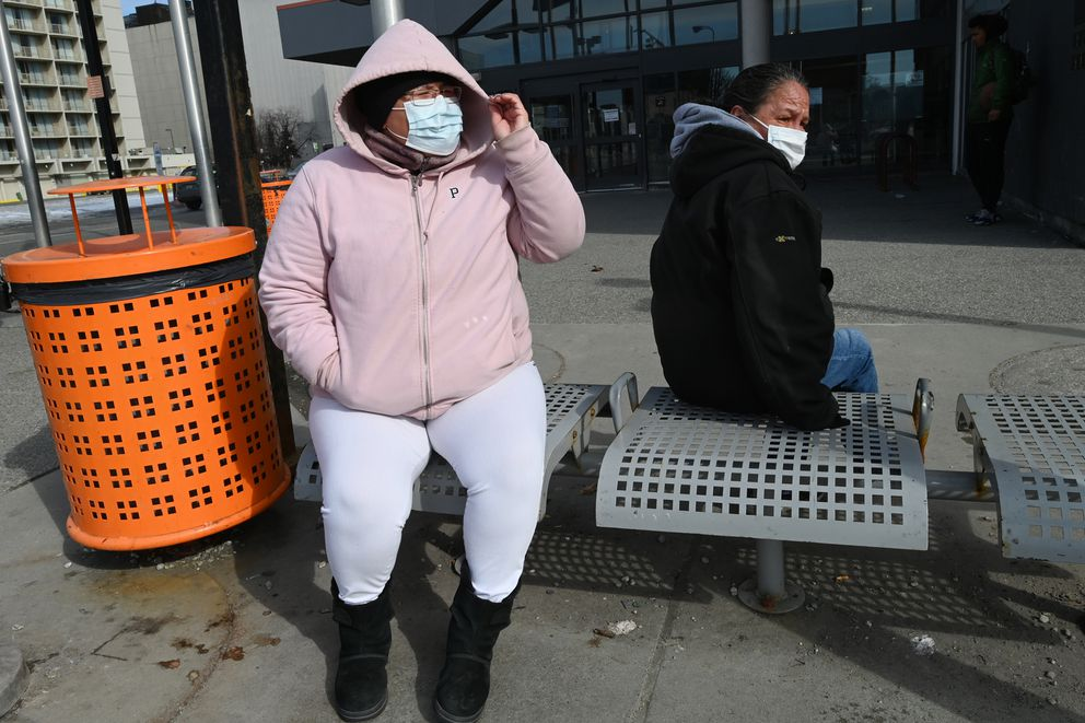 Melissa Jack, left, waits for a bus at the downtown transit center on Sunday, April 5, 2020. Jack said she wore a mask for the first time because she was riding the bus. People Mover will temporarily suspend fixed-route service at 11:59 p.m. on Wednesday, April 8. (Bill Roth / ADN)