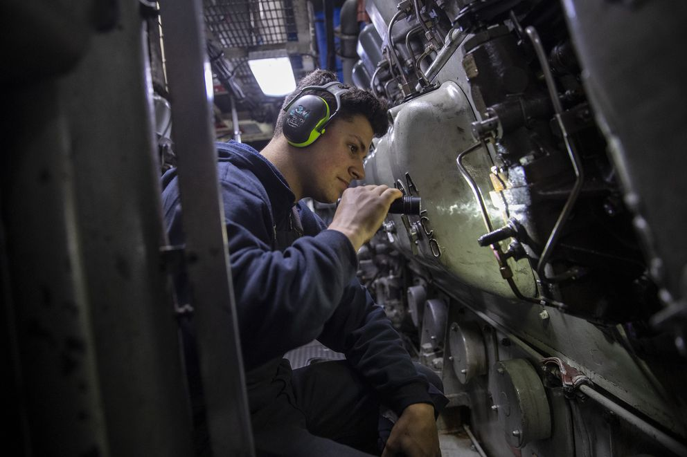 Engineer Michael Malanga peers inside one of the massive diesel engines aboard the US Coast Guard cutter Polar Star as the heavy ice breaker is underway from Seattle to a dry dock on Mare Island during voyage from Seattle, Wash., on April 21, 2019. (Brian van der Brug / Los Angeles Times/TNS)