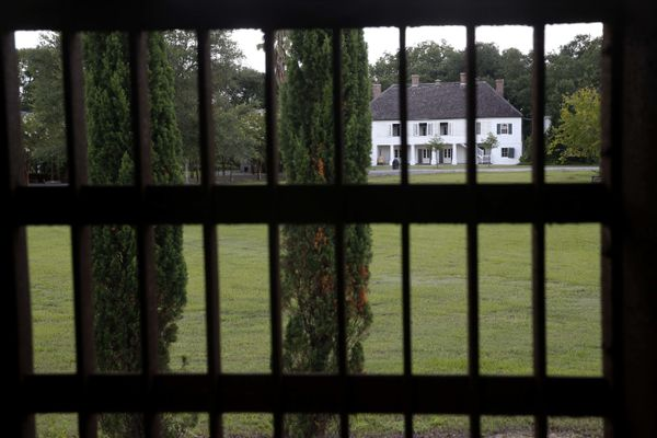 In this July 14, 2017 photo, the main plantation house is seen through the bars of a jail, similar to one's used for slaves, at the Whitney Plantation in Edgard, La. Owner John Cummings opened Whitney more than two years ago as a slavery museum, bucking a tradition of plantation tours that romanticize antebellum life and gloss over the slave trade. (AP Photo/Gerald Herbert)