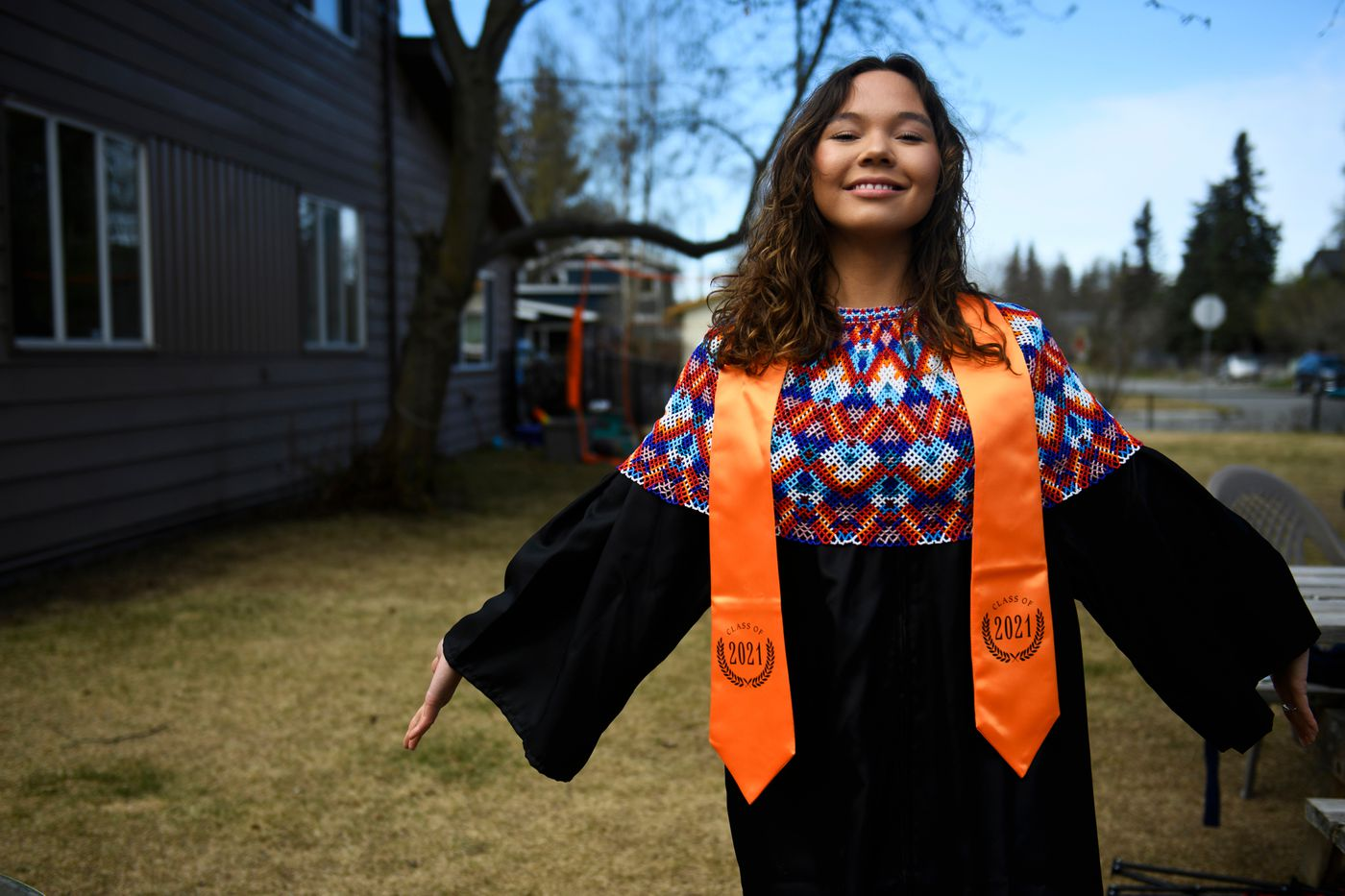 Ivalu Blanchett decided not to attend the West High School graduation after she was told she couldn't wear her Greenlandic shawl over her gown. Instead, she had a private graduation ceremony in her yard. (Marc Lester / ADN)