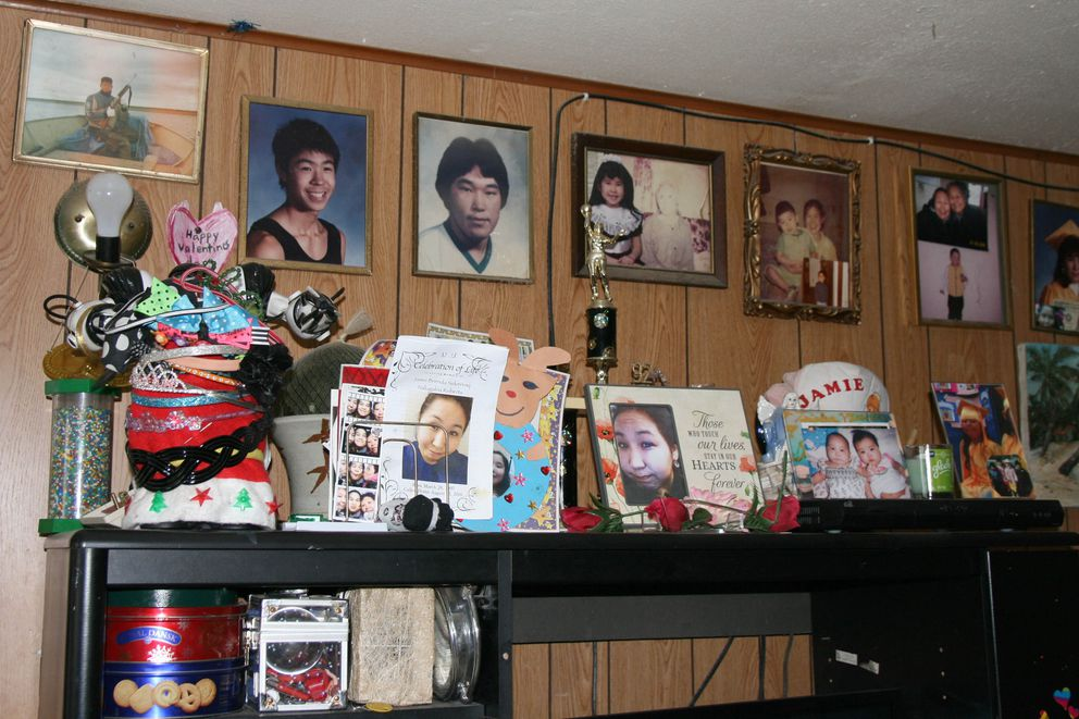 Family photos line the walls and shelves of the Roberts home in Quinhagak, Alaska, on Sept. 15, 2016. Remembrances of Jamie, 19, are in the center. She died a month earlier from a heroin overdose. (Lisa Demer / Alaska Dispatch News.)