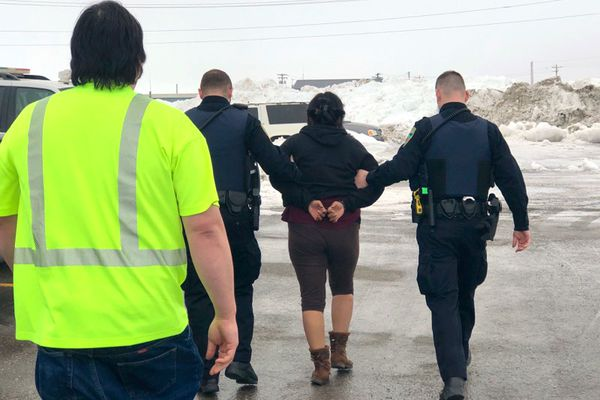 Nome police lead away a woman identified by friends as Brenda Evak after she was arrested Wednesday, March 27 2019 at the Nome airport during a protest of Gov. Mike Dunleavy's visit. (Photo by Sue Steinacher)