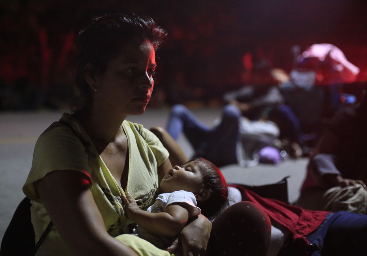 A woman holding her sleeping baby waits in hopes of hitching a ride, as a thousands-strong caravan of Central Americans continues its slow march toward the U.S. border, in Tapanatepec, Oaxaca state, Mexico, before dawn on Monday, Oct. 29, 2018. Thousands of migrants traveling together for safety resumed their journey after taking a rest day Sunday, while hundreds more migrants were pushing for entry to Mexico.(AP Photo/Rebecca Blackwell)