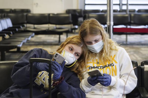 Rachel Miner, 15, left, of Emmetsburg, Iowa, sits with Carlotta Haas, 15, a foreign exchange student from Duesseldorf, Germany, who had been living with Miner and her family but was called home, as they waited for her flight Wednesday, March 25, 2020, in at Minneapolis-St. Paul International Airport in Minneapolis. (Anthony Souffle/Star Tribune via AP)