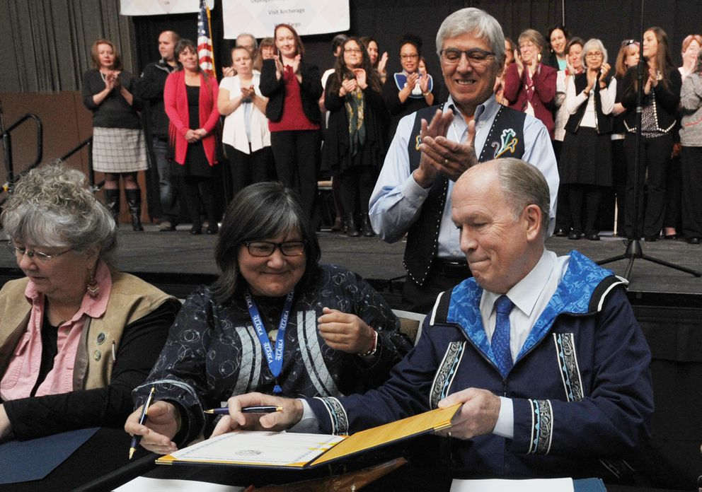 Department of Health and Social Services Commissioner Valerie Davidson, center, and Gov. Bill Walker sign the historic Alaska Tribal Child Welfare Compact on the first day of AFN at the Dena'ina Center in Anchorage on Oct. 19, 2017. (Bill Roth / ADN)