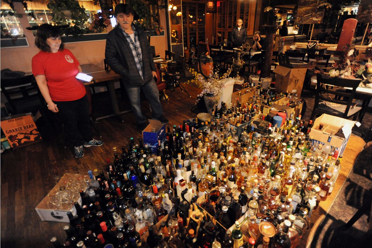 Ulber Ferati and his wife Urime, owners of Fiori D' Italia in Spenard looks at liquor bottles salvaged after the 7.0 earthquake knocked the bottles off shelves behind the bar on Friday, Nov. 30, 2018. (Bill Roth / ADN)