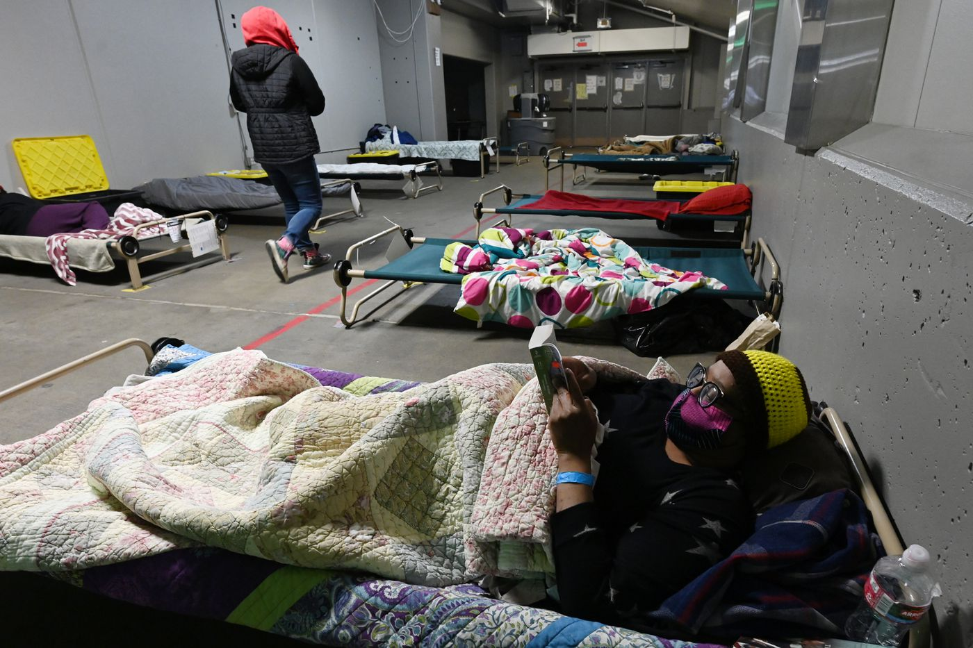 Roxanne Jnolewis reads a book in the Mass Emergency Shelter operated by Beans's Cafe in Sullivan Arena on Feb. 24, 2021. Jnolewis said at the time that she had been staying at the shelter since the end of last May and was on a waiting list for housing and other services. (Bill Roth / ADN)