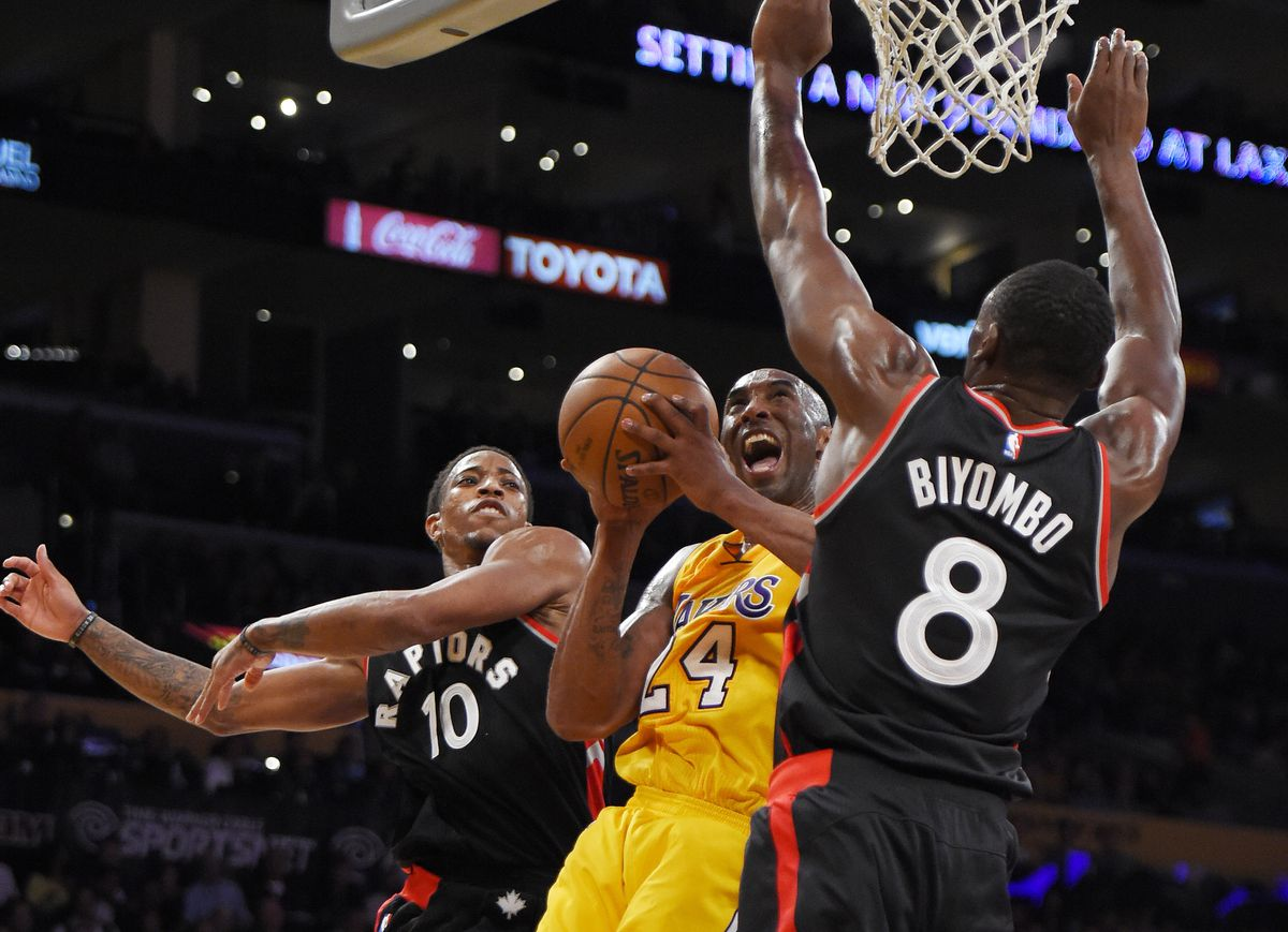 FILE - In this Nov. 20, 2015, file photo, Los Angeles Lakers forward Kobe Bryant, center, shoots as Toronto Raptors guard DeMar DeRozan, left, and forward Bismack Biyombo, of Congo, defend during the second half of an NBA basketball game, in Los Angeles. Bryant, the 18-time NBA All-Star who won five championships and became one of the greatest basketball players of his generation during a 20-year career with the Los Angeles Lakers, died in a helicopter crash Sunday, Jan. 26, 2020. (AP Photo/Mark J. Terrill, File)