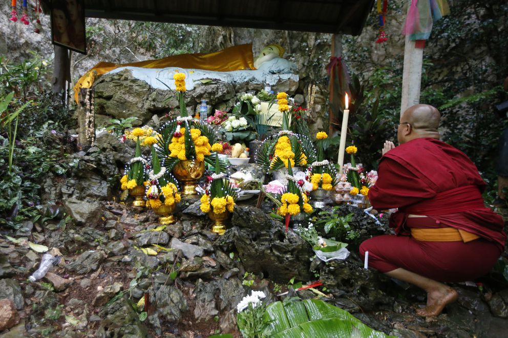 FILE - In this June 27, 2018, file photo, a Thai Buddhist monk prays for 12 boys and their soccer coach, in Mae Sai, Chiang Rai province, northern Thailand. For the boys and their coach, we have only a hint of what it might have been like. But for the rest of us, watching from afar as the world's journalists beamed us live shots and the unknowable became known drip by captivating drip, we knew only one thing: It was hard to look away. (AP Photo/Sakchai Lalit, File)