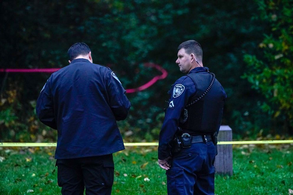 Crime scene investigator Sean Keating, left, talks with officer Derek Detherow at the scene of a homicide in Russian Jack Springs Park on Friday morning, Sept. 25, 2020. (Loren Holmes / ADN)