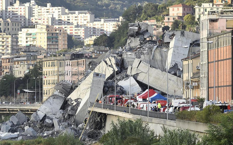 Rescuers work to recover an injured person after the Morandi highway bridge collapsed in Genoa, northern Italy, Tuesday, Aug. 14, 2018. The highway bridge collapsed during a violent storm, sending vehicles plunging 45 meters (nearly 150 feet) into a heap of rubble. Authorities said at least 20 people were killed, although some people were found alive in the debris. (Luca Zennaro/ANSA via AP)