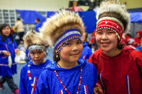 From left, Toksook Bay residents Panik Chimiugak, 10, Catherine Lincoln, 14, and Cadence Dull, 10, wait backstage before their performance at the Cama-i Dance Festival in Bethel on Saturday, April 18, 2015. Thousands of spectators joined hundreds of dancers, drummers and artists for the annual festival. (Tara Young / ADN)