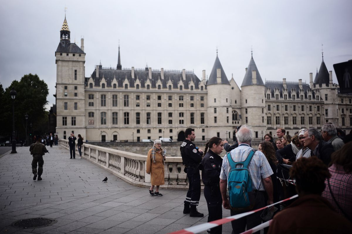 People stand behind a police tape as they are evacuated nearby the police headquarters after a knife attack in Paris, Thursday, Oct. 3, 2019. (AP Photo/Kamil Zihnioglu)
