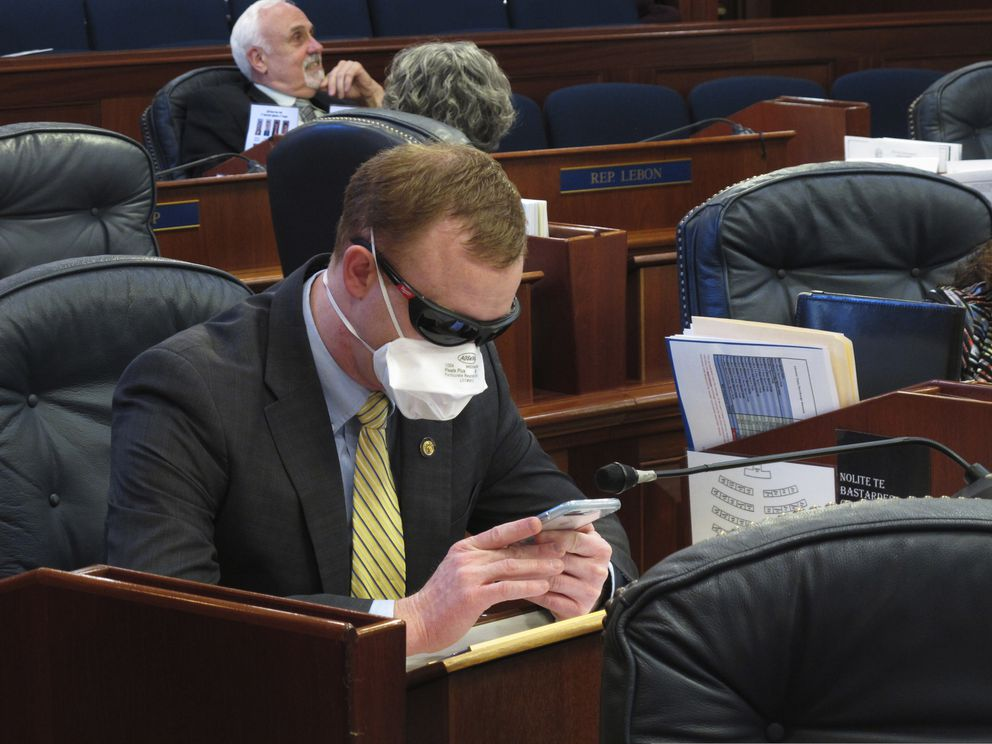 Alaska state Rep. David Eastman sits at his desk on the House floor in Juneau, Alaska, Monday, March 23, 2020. Eastman, a Wasilla Republican, has been critical of the Legislature's planning around the coronavirus. Rep. Sharon Jackson also wore a mask on the House floor Monday. (AP Photo/Becky Bohrer)