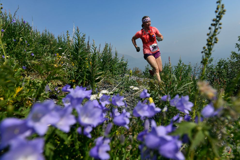 Wendy Terry, of Anchorage, runs by wildflowers during the Mount Marathon women's race on July 4, 2019, in Seward. (Marc Lester / ADN)