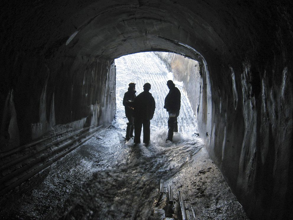 This undated photo provided by the U.S. Army Corps of Engineers shows people standing inside a water tunnel leading from a diversion dam on Lowell Creek high above the town of Seward, Alaska. Beginning every fall, heavy storms test Seward's antiquated flood-control system, leading to fears of a major disaster should it finally fail after nearly eight decades of diverting a fast-moving creek away from its historical route through town. Officials say a tunnel that carries flood waters from Lowell Creek to Resurrection Bay could get clogged by tree stumps or boulders. In that scenario, water would overflow the diversion dam at the tunnel entrance, rushing down a main thoroughfare. (U.S. Army Corps of Engineers via AP)