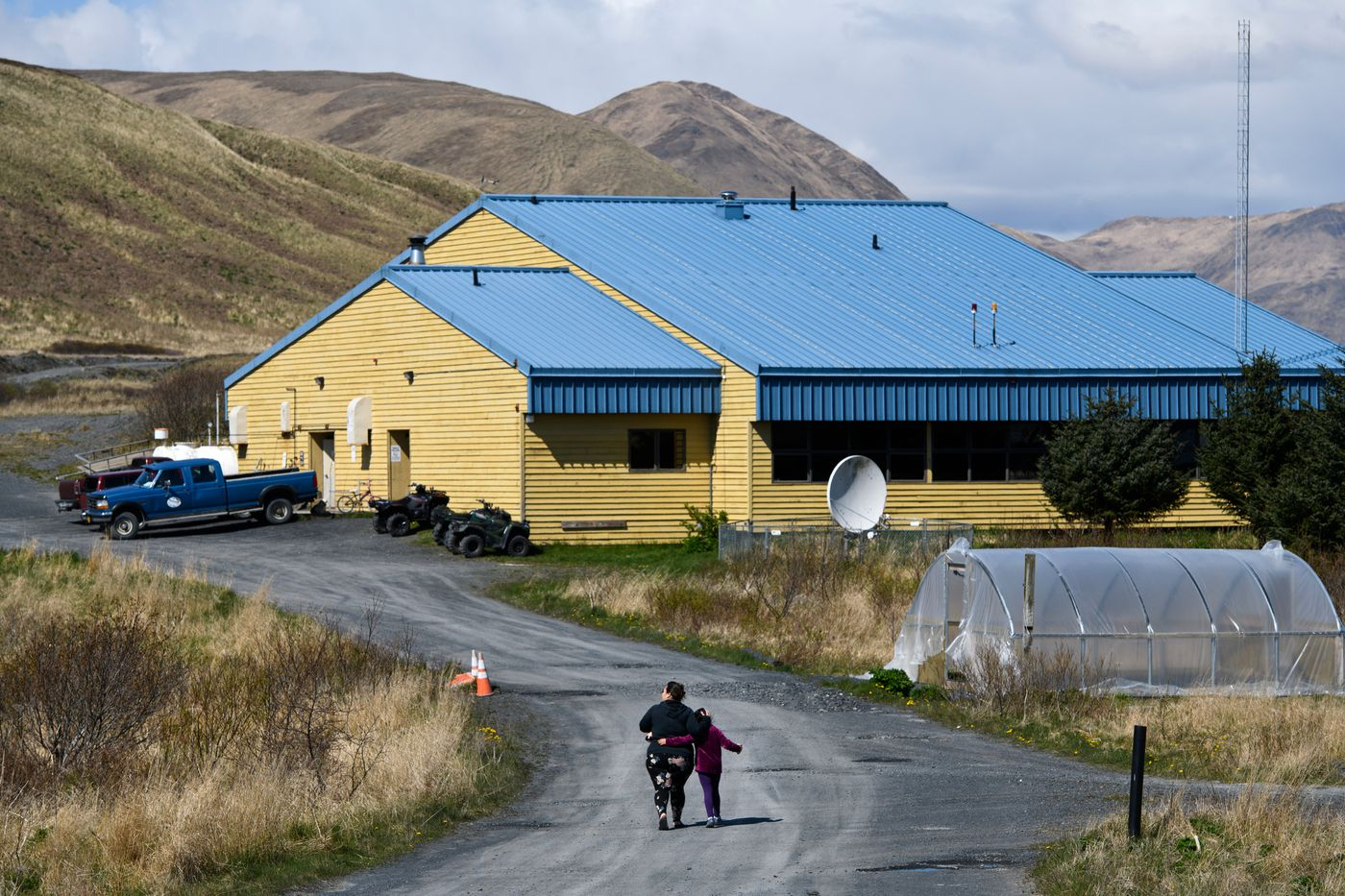 Akhiok residents walk to the school for an Alutiiq dance rehearsal on May 14. The Akhiok School finished the school year with 13 students in kindergarten through 12th grade. (Marc Lester / ADN)