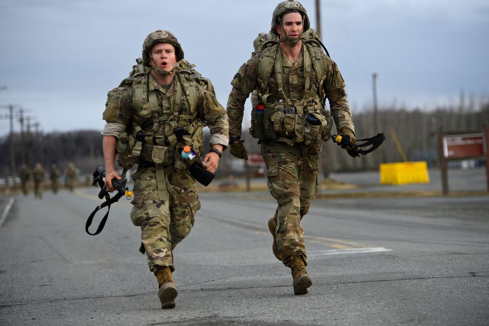 Paratroopers finish a 12-mile road march carrying about 70 pounds of gear on April 30, 2021. Expert Infantry and Expert Soldier Badge testing concluded Friday with a 12-mile road march and an award ceremony. (Marc Lester / ADN)