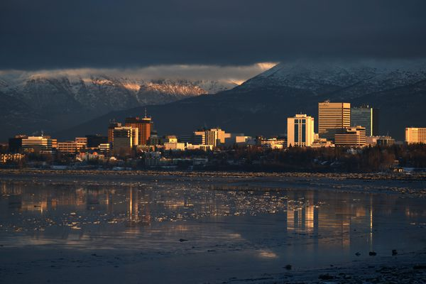 The setting sun lights up the Anchorage Skyline in front of the Chugach Mountains on Wednesday, Dec. 6, 2017. (Bob Hallinen / ADN)