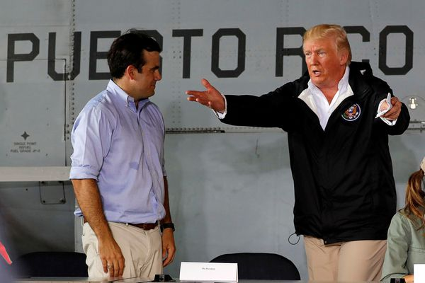U.S. President Donald Trump talks with Puerto Rico Governor Ricardo Rossello (L) as they take their seats for a briefing on hurricane relief efforts in a hangar at Muniz Air National Guard Base in Carolina, Puerto Rico, U.S. October 3, 2017. REUTERS/Jonathan Ernst