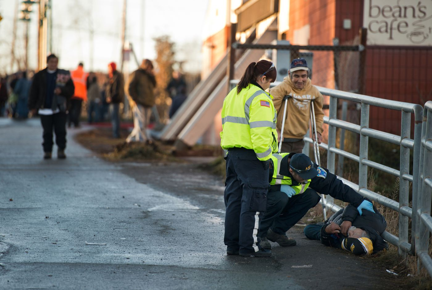 "Anchorage Safety Patrol driver Pam Garner, left, and EMT Garrett Sey, kneeling, respond to a man on the ground near Bean's Cafe. Garner said she does occasionally get burned out at her job. ""Because it's just an everyday thing and you see the same people over and over,"" she said. Photographed on Wednesday, November 19, 2014. Marc Lester / ADN"