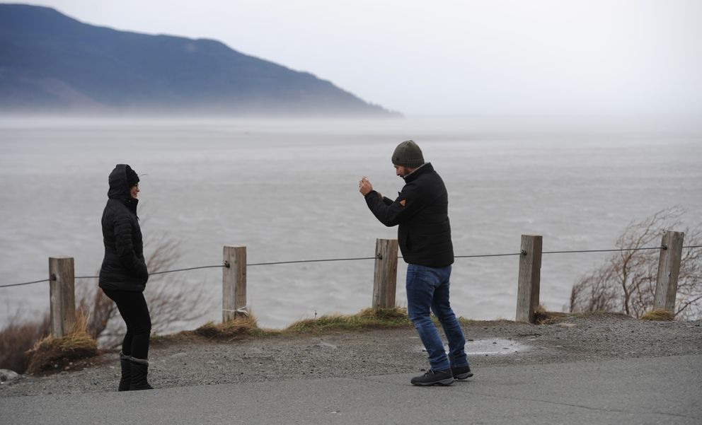 Beatriz Landaverde and her husband Esdras Landaverde who are visiting from Los Angeles lean into the wind while taking photos at Beluga Point while traveling along the Turnagian Arm on Sunday, Oct. 27, 2019. (Bill Roth / ADN)