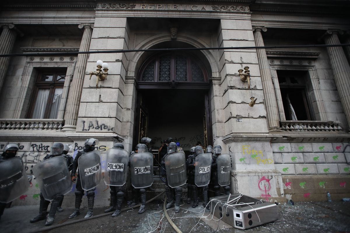 Police surround the Congress building after protesters set it on fire, in Guatemala City, Saturday, Nov. 21, 2020. Hundreds of protesters were protesting in various parts of the country Saturday against Guatemalan President Alejandro Giammattei and members of Congress for the approval of the 2021 budget that reduced funds for education, health and the fight for human rights. (AP Photo/Moises Castillo)