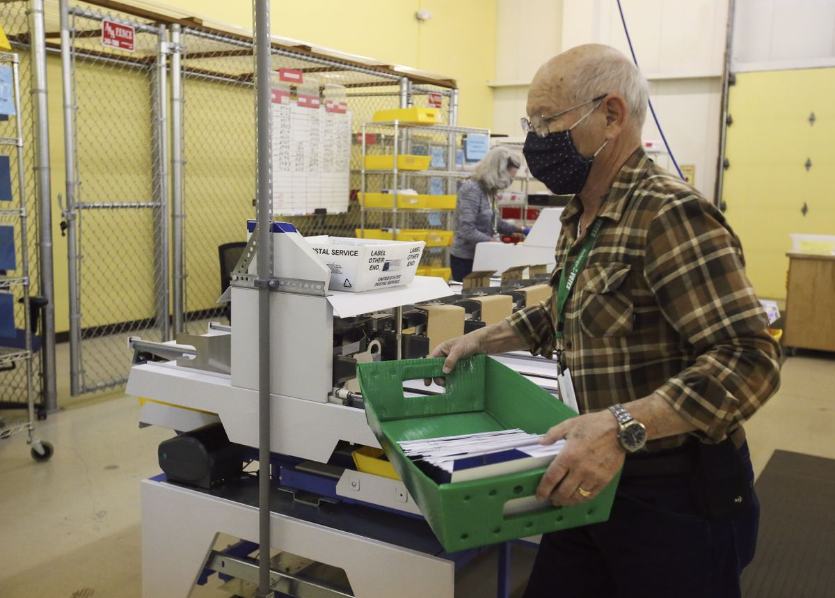 Jerry Laycock transfers a box of election ballot envelopes to a shelf for processing at the MOA Election Center in Anchorage on Wednesday, May 12, 2021. (Emily Mesner / ADN)
