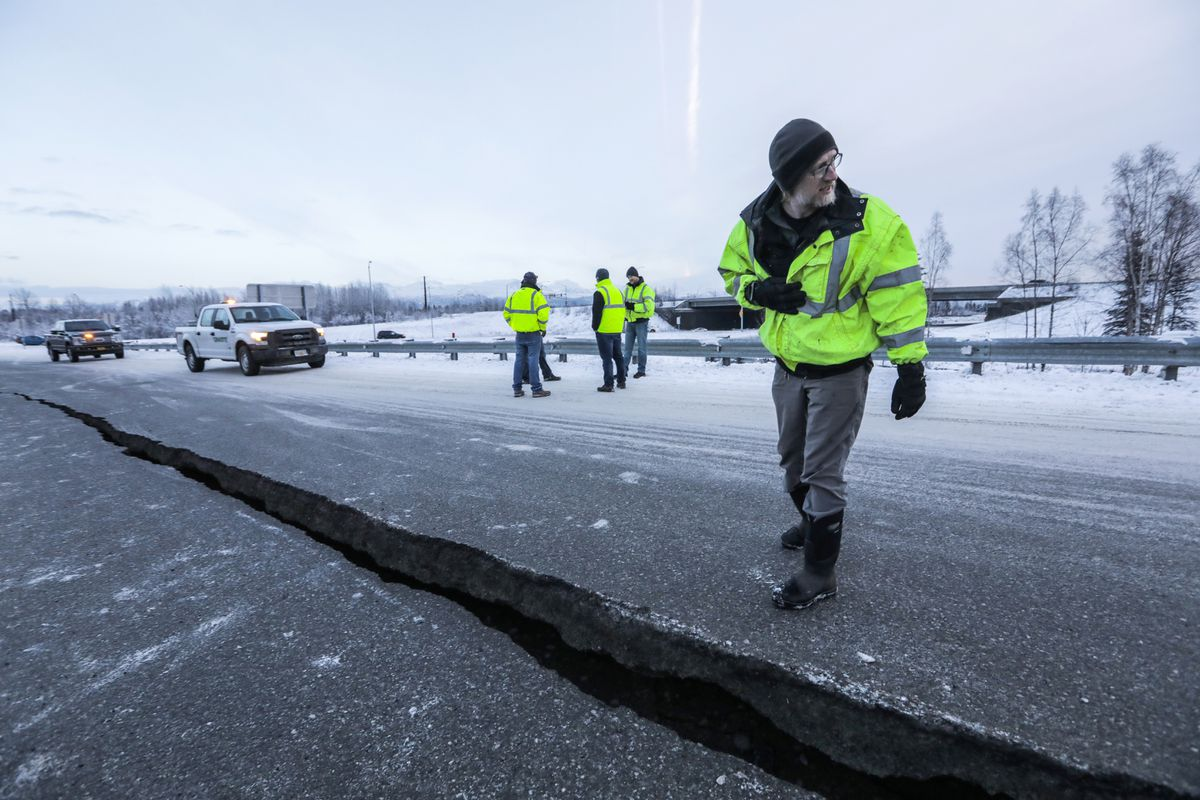 DOT engineer assistant Chris Riekena inspects a crack in the road at the International Airport Road offramp on southbound Minnesota Blvd. Friday, Nov. 30, 2018. (Loren Holmes / ADN)