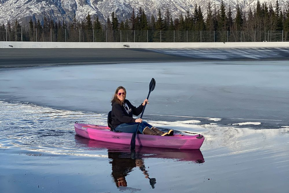 Alaska Raceway Park owner Michelle Lackey Maynor kayaks across track's infield, which after a snowy winter had turned into a big pool of water on Thursday, April 15, 2021. The Palmer track has since dried and is ready for Sunday's season-opening races. (Photo courtesy Alaska Raceway Park)