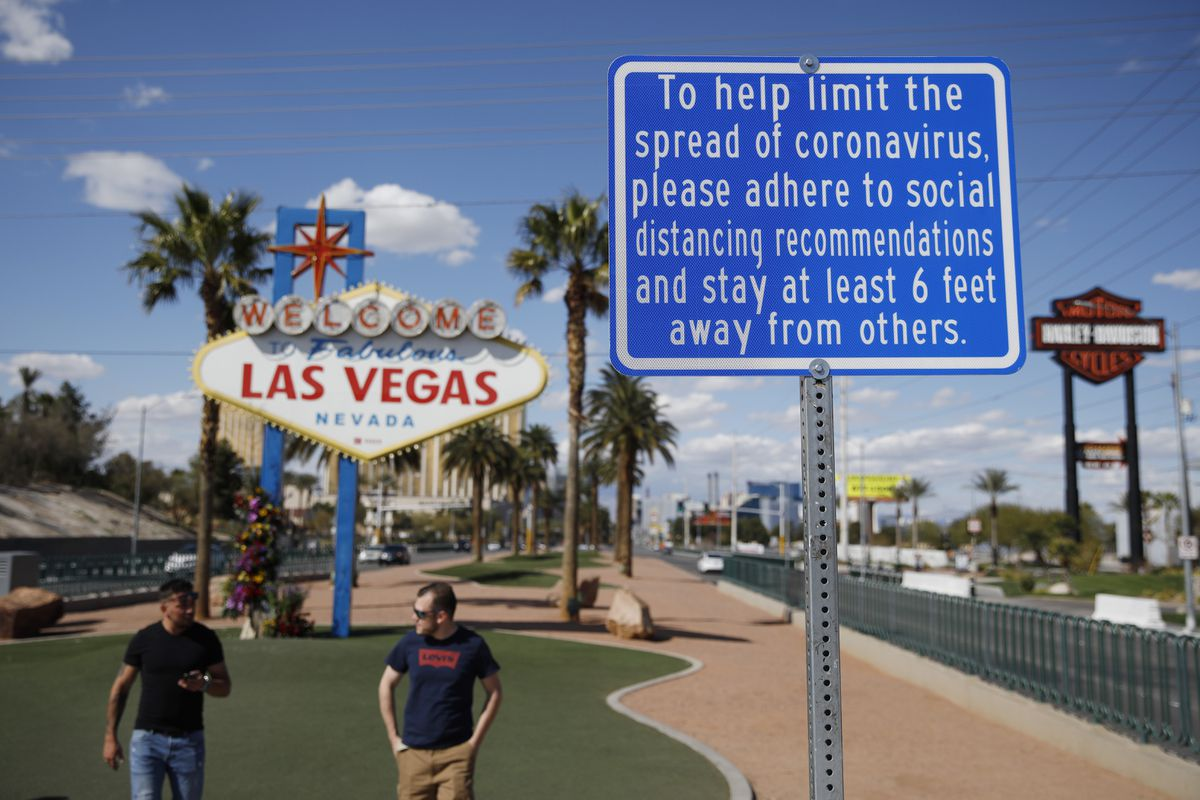 FILE - In this March 21, 2020 file photo, a sign advises people to practice social distancing to slow the spread of the coronavirus at the