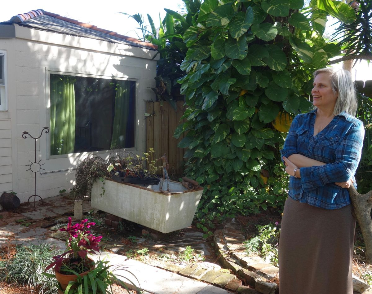 Deb Long stands in the courtyard outside her New Orleans home. (Photo by Ned Rozell)