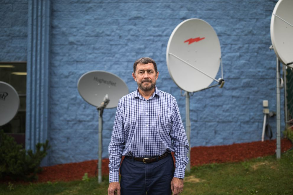 Microcom vice president Chuck Schumann stands next to some of his company's satellite dishes outside its Anchorage office recently. Microcom is a major player in Alaska's satellite internet market, and Schumann questioned whether OneWeb will be able to provide broadband service. (Loren Holmes / Alaska Dispatch News)