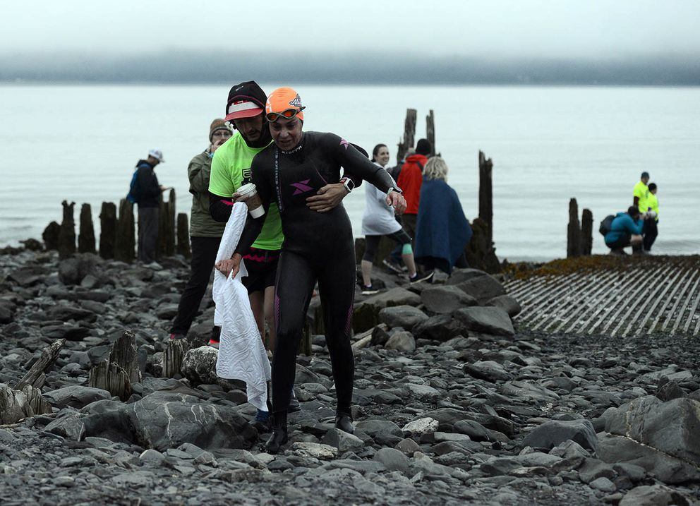 The first swimmer out of the water is helped up the ramp from Resurrection Bay. (Photo by Erik Hill)