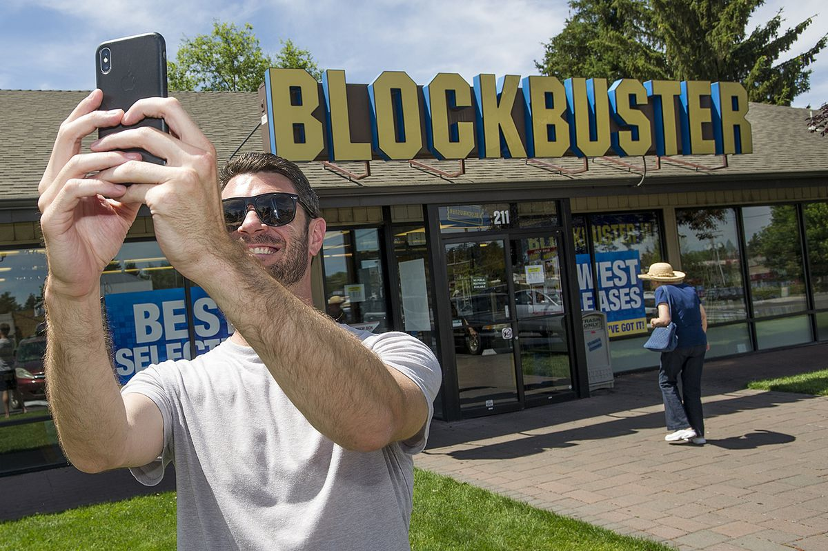 Scott Thornton takes a selfie in front of the Bend, Ore., Blockbuster on Friday, July 13, 2018. The Bend store is the last remaining Blockbuster in operation in the United States after two stores in Alaska closed earlier this week. (Ryan Brennecke /The Bulletin via AP)