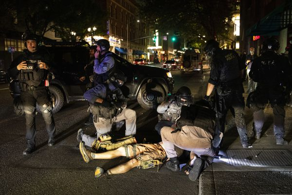 ADDS THE SHOOTING WAS FATAL - A man is treated after being shot Saturday, Aug. 29, 2020, in Portland, Ore. It wasn't clear if the fatal shooting late Saturday was linked to fights that broke out as a caravan of about 600 vehicles was confronted by counterdemonstrators in the city's downtown. (AP Photo/Paula Bronstein)