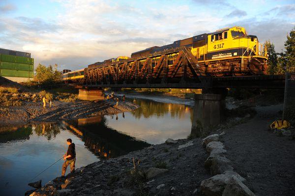 Alex Tuny fishes forsilvers as an Alaska Railroad passenger train passes by. (Bob Hallinen / ADN)