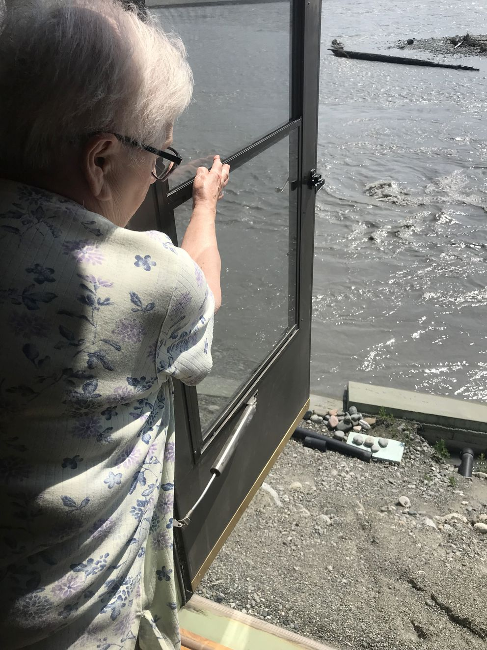 Val Musial opens her backdoor, revealing how close the river is to their home, June 26, 2019. The house is endangered by the eroding banks of the Matanuska River. (Zaz Hollander / ADN)