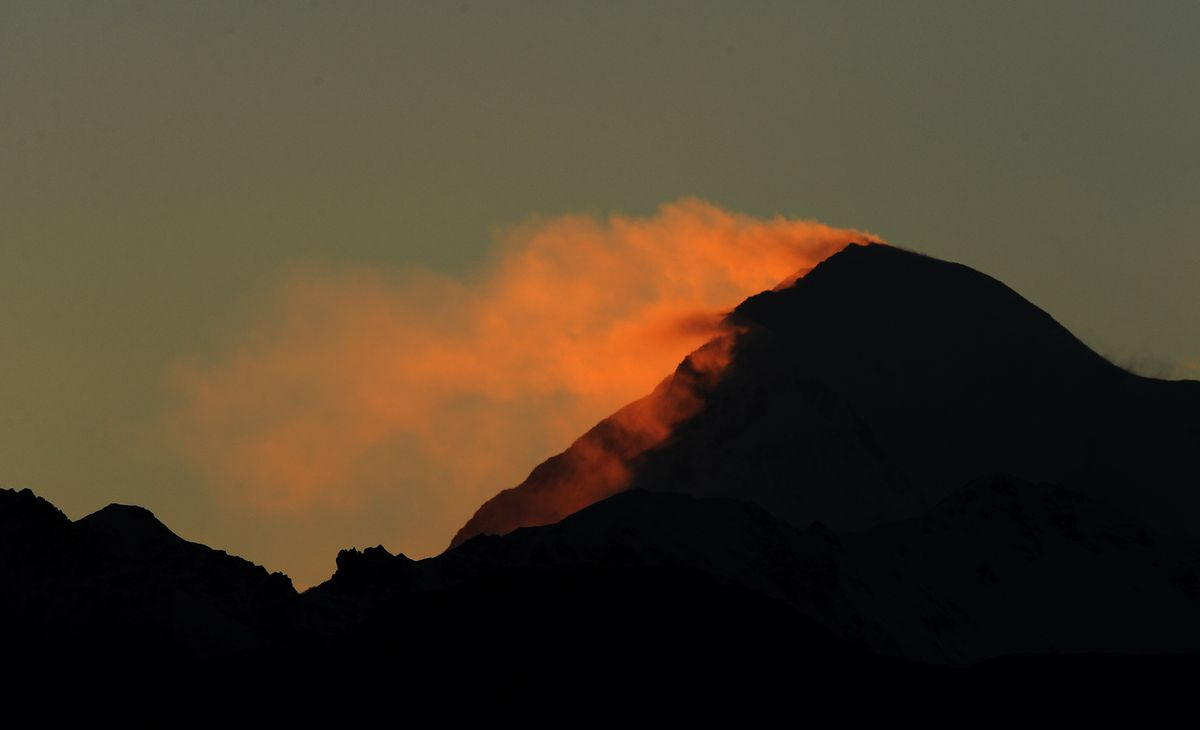 Snow illuminated by the setting sun blows off the top of Denali. (Bob Hallinen / ADN)