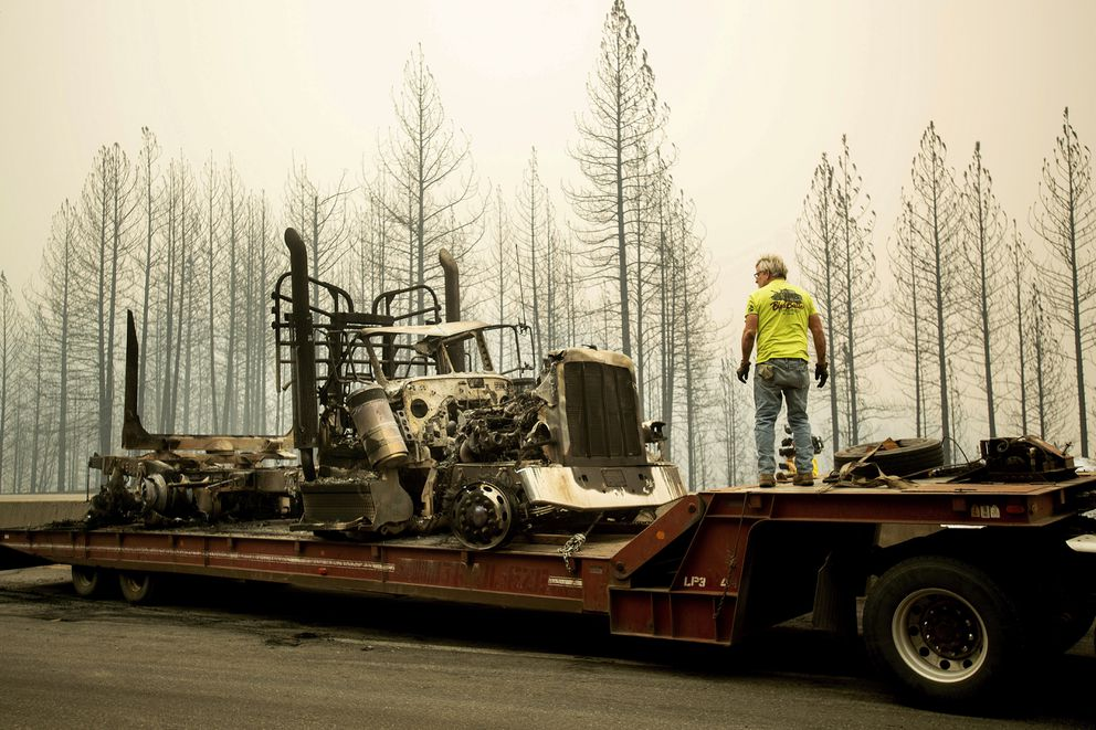 Bruce Palmer prepares to tow a truck scorched by the Delta Fire on Interstate 5 in the Shasta-Trinity National Forest, Calif., near Shasta Lake on Thursday, Sept. 6, 2018. The highway remains closed to traffic in both directions as crews battle the blaze. (AP Photo/Noah Berger)