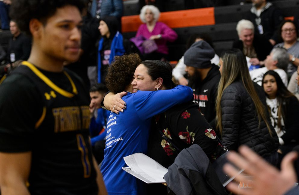 As Daishen Nix is interviewed after a game, his mother Mina Tupuola is greeted by another player. (Marc Lester / ADN)