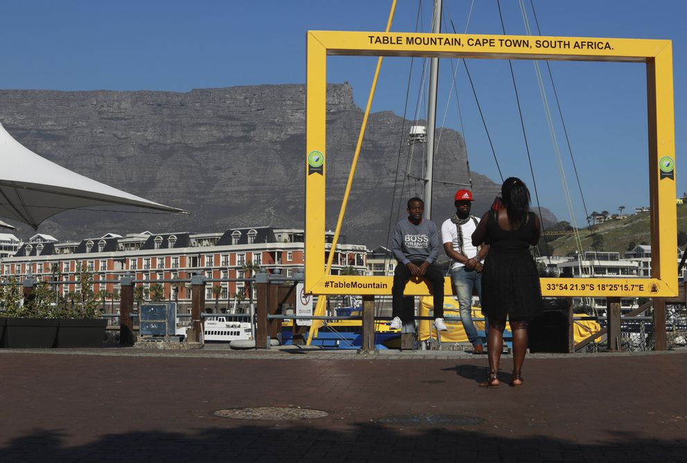 Visitors to Cape Town's popular V&A Waterfront are photographed against a backdrop of the city's Table Mountain, Friday, July 31, 2020. For growing numbers of businesses and individuals who depend on the global tourism industry, the question is not so much when the coronavirus pandemic will end but how and if they'll survive until business picks up. (Photo/Nardus Engelbrecht)
