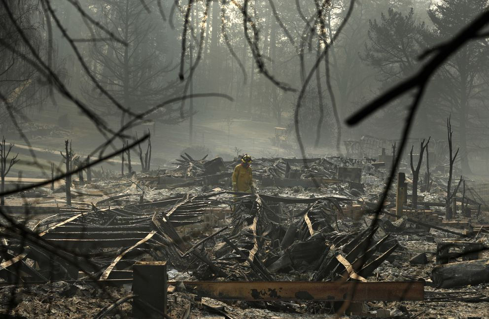 A firefighter searches for human remains in a trailer park destroyed in the Camp Fire, Friday, Nov. 16, 2018, in Paradise, Calif. (AP Photo/John Locher)