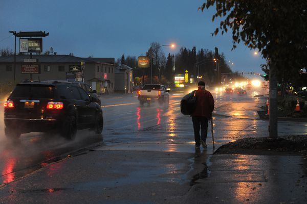 With his sleeping bag over his shoulder Doug Shepard walks away from the Anchorage Gospel Rescue Mission along Tudor Road in Anchorage, Alaska on Thursday, Oct. 12, 2017. Shepard who is homeless has timed out at the mission. (Bob Hallinen / Alaska Dispatch News)