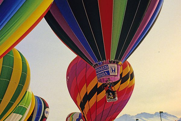 Balloons lift off from downtown Anchorage for the 1984 Fur Rendezvous balloon race. Photo by Al Geist/Geist Arts