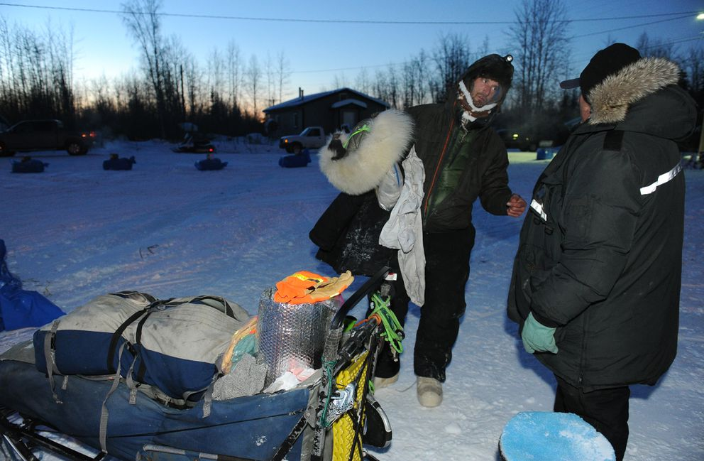 Nicolas Petit talks with Patrick Moore, president of the Tanana dog mushing association, after reaching the checkpoint to claim the prize for being the first musher to reach the Yukon River. (Bob Hallinen / Alaska Dispatch News)