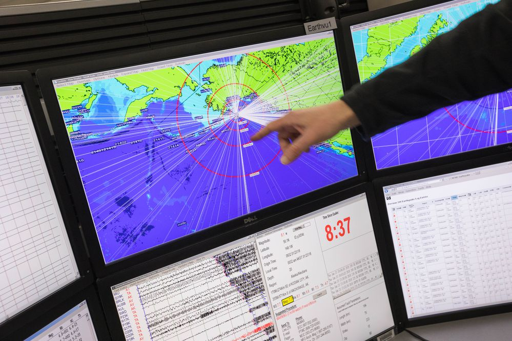 Ken Macpherson, a watchstander at the National Tsunami Warning Center in Palmer, gestures Tuesday, Jan. 23, 2018 at a display showing the magnitude 7.9 earthquake that occurred earlier in the morning, generating a tsunami warning for most coastal communities in the Gulf of Alaska. Macpherson was working overnight when the earthquake occurred at 12:31 A.M. (Loren Holmes / ADN)