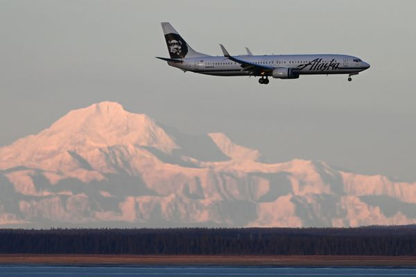 An Alaska Airlines passenger jet lands at Ted Stevens Anchorage International Airport on Wednesday, Dec. 18, 2019, with Denali visible in the distance. (Bill Roth / ADN)